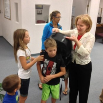 """Ethan and our other children try on the """"missions backpack."""" This backpack contains tools and resources to hike into hard-to-reach areas to present the gospel."""